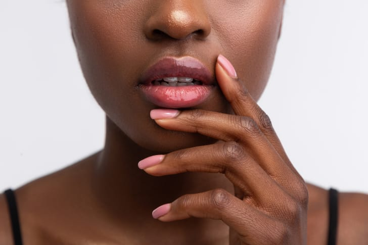 Young woman wearing shiny lip gloss