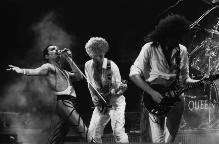 Freddie Mercury, John Deacon, and Brian May of British rock group Queen in concert in 1984.