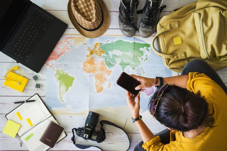 Young woman uses a map to plan a vacation