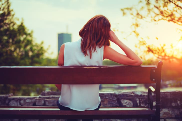 Young woman sits on bench and stares into the distance
