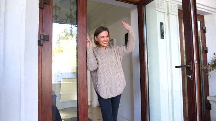 Happy woman waves from her front door