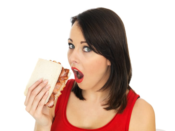Young woman eating a bacon sandwich