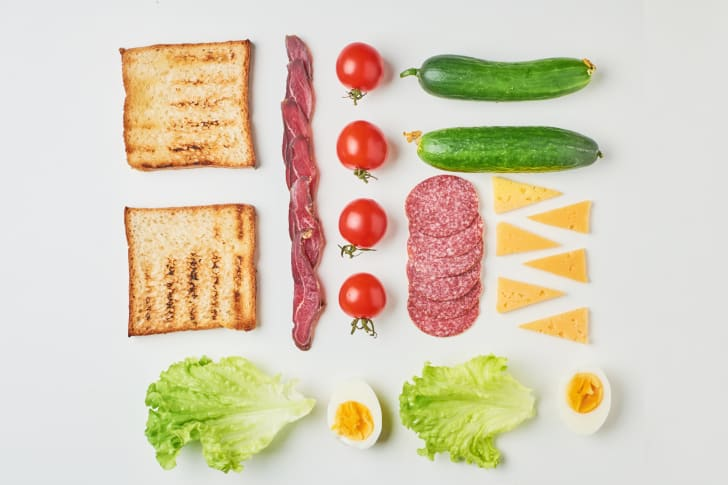 Several sandwich ingredients against a white background