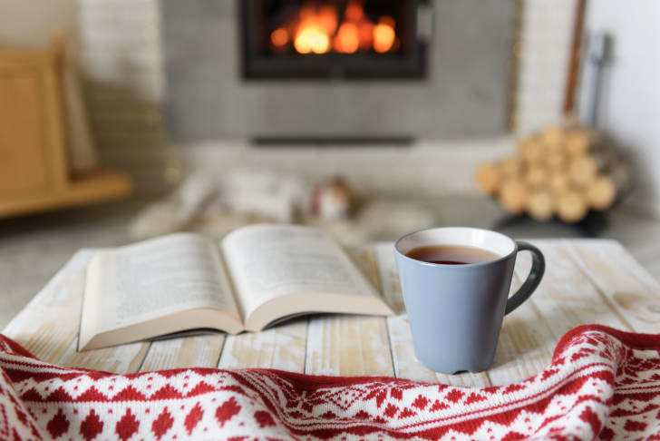 Book and cup of tea by a cozy fire