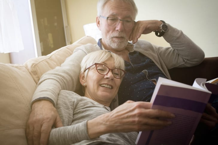 An older couple relaxes by reading a book together