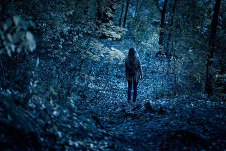 Woman walking alone on path in mystic dark forest