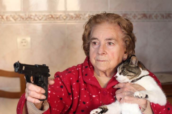 Elderly woman points a gun while protecting her cat