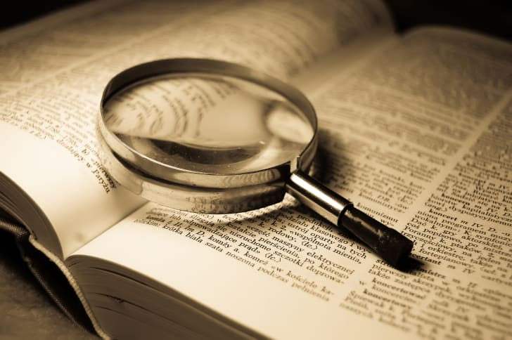 A magnifying glass on top of an open dictionary.