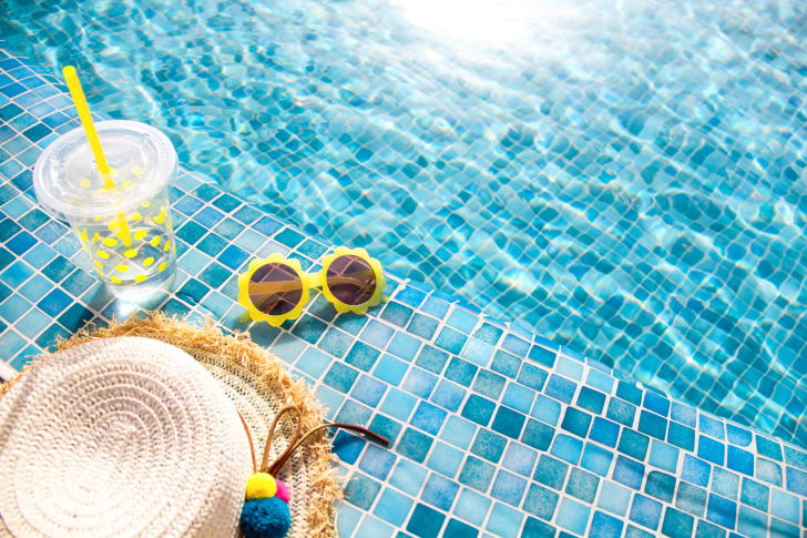 A hat and sunglasses next to a pool.