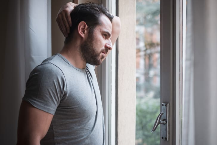 A man anxiously looking out of a window.