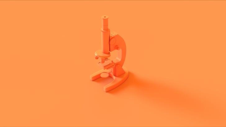 An orange microscope on an orange background.