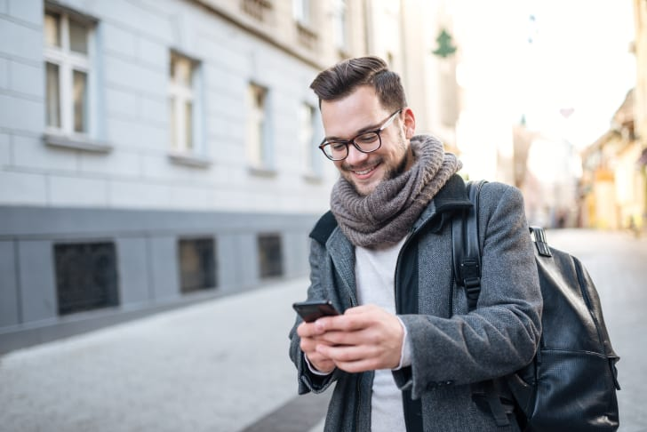 A young man wearing a scarf smiling at his smartphone