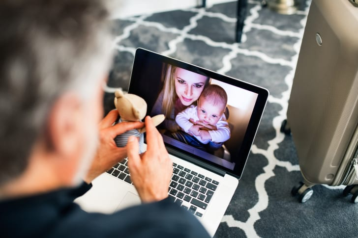 A man holds a toy while video calling a woman and child