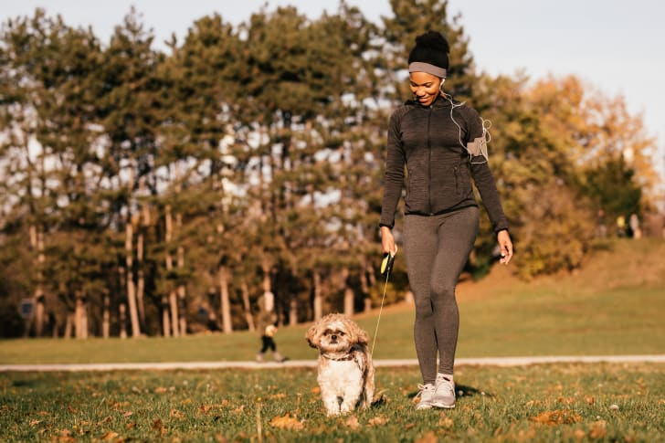 A woman walking her dog in the park