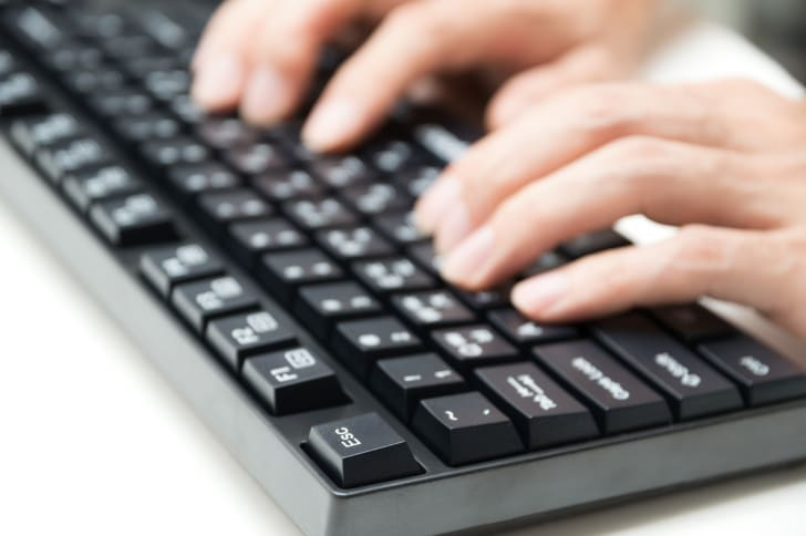 A person typing on a keyboard.