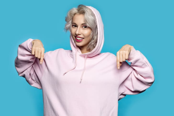 A young woman in a pink sweatshirt against a blue background