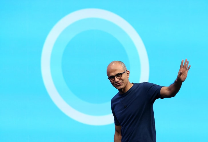 A man in front of the logo for Cortana.