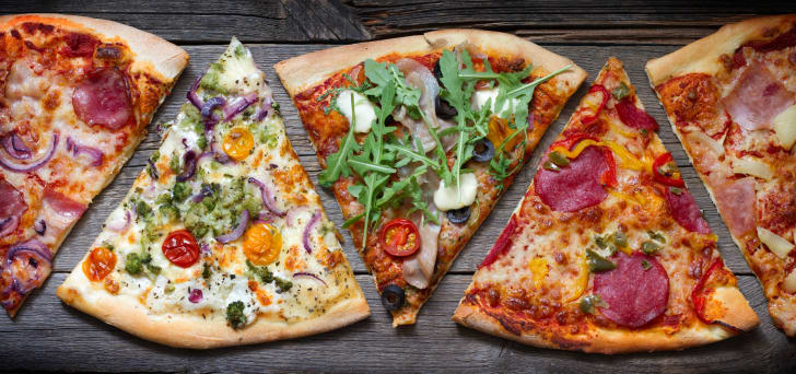 Slices of different kinds of pizza on a wooden table.