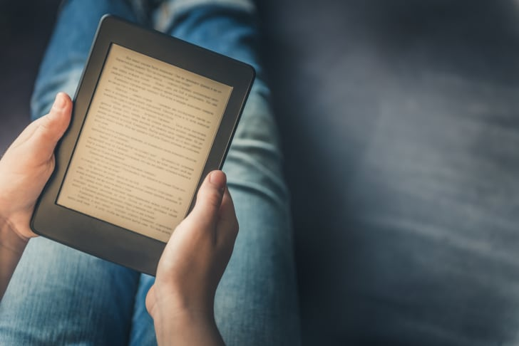 A person reading on a Kindle.