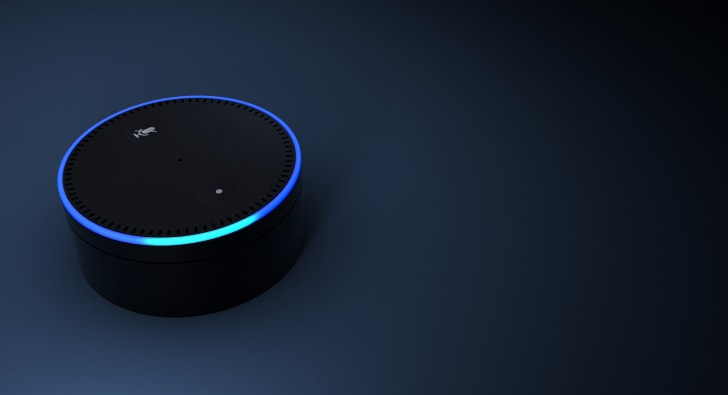 An Amazon dot lit up on a dark blue table.