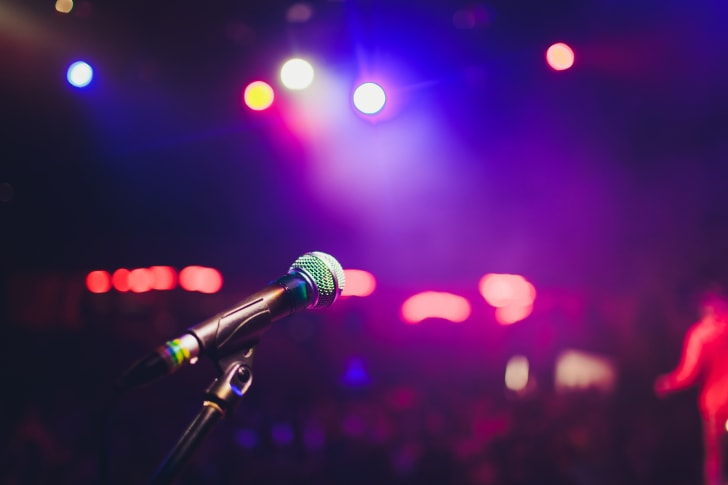 A microphone in front of a blurry purple background