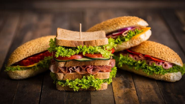 A number of sandwiches on a wooden table