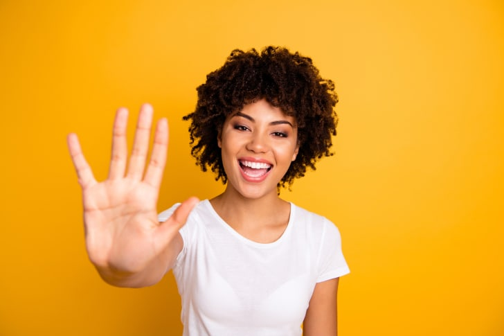 A woman high fiving in front of a yellow background