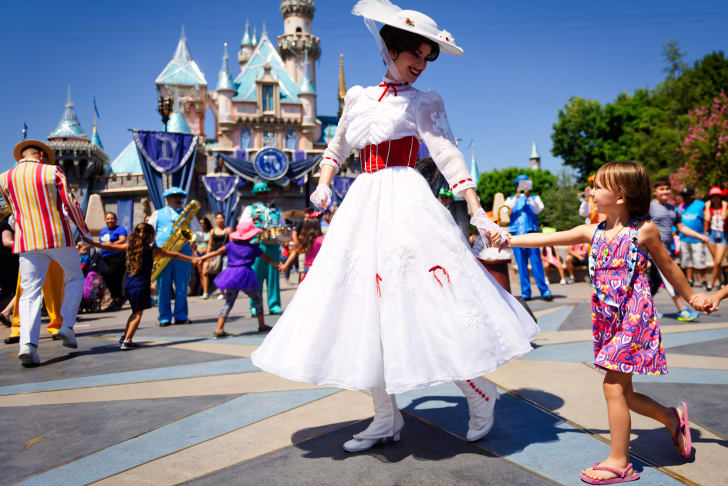 A woman dressed as Mary Poppins holds a young girl's hand on a sunny day at Disneyland