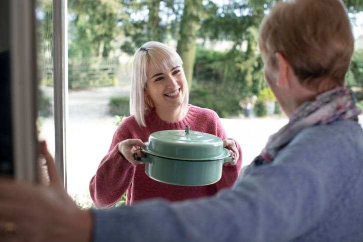 Woman giving a casserole to a neighbor