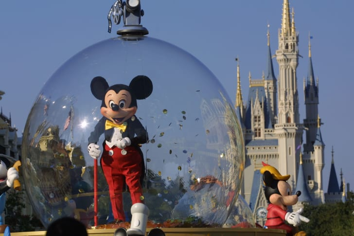 Mickey Mouse surveying the crowd while inside a protective bubble.