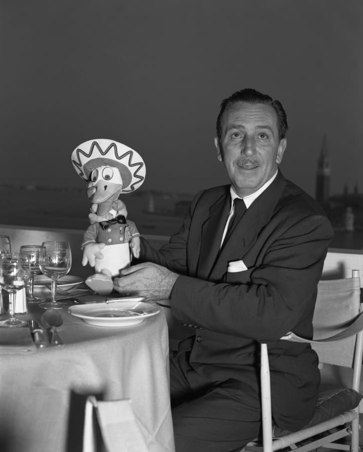 Walt Disney holding an early Donald Duck collectible.