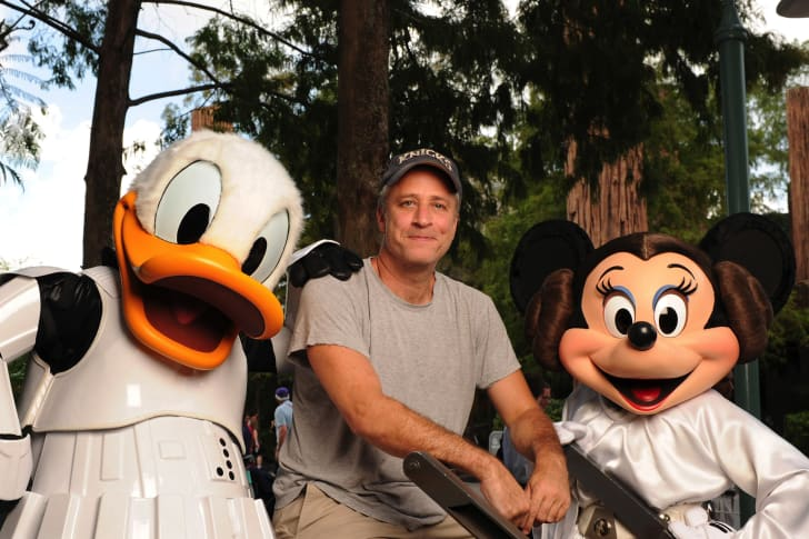 Jon Stewart posing with Donald Duck and Minnie Mouse.
