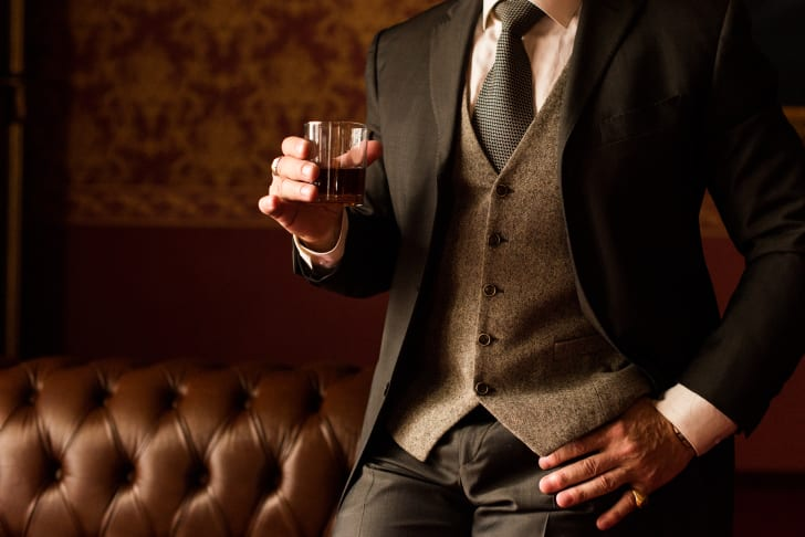 Man in brown suit holding a drink