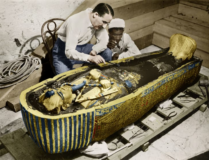English Egyptologist Howard Carter examines the golden sarcophagus of Tutankhamun in Egypt in 1923.