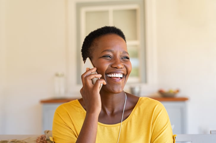 A woman talking on the phone laughing.