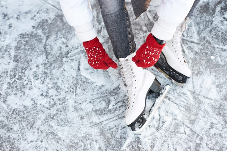 A woman putting on ice skates.