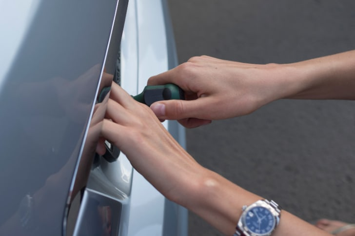 A man is pictured securing a license plate to a car