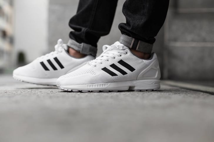 A pair of feet wearing white Adidas sneakers
