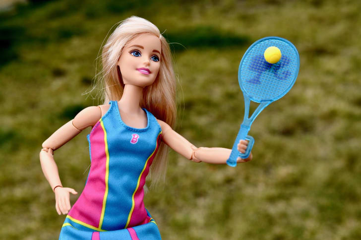 A Barbie doll posed as if playing tennis.