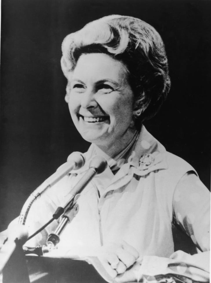 American political activist Phyllis Schlafly smiles from behind a pair of podium mounted microphones, 1982