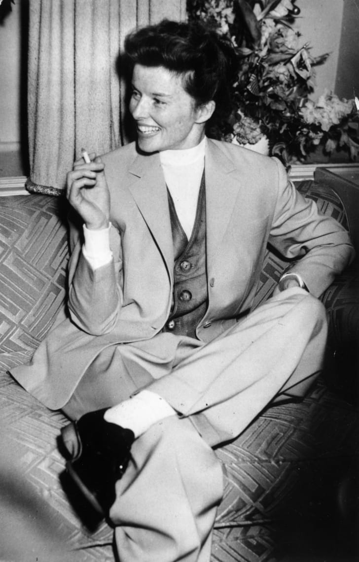 katharine hepburn wearing pants and smoking a cigarette in london