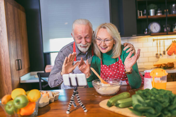 Senior couple making video call on phone in modern kitchen.