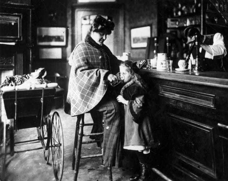 A mother gives her daughter a drink at the bar of a public house, while the baby sleeps in a pram beside her