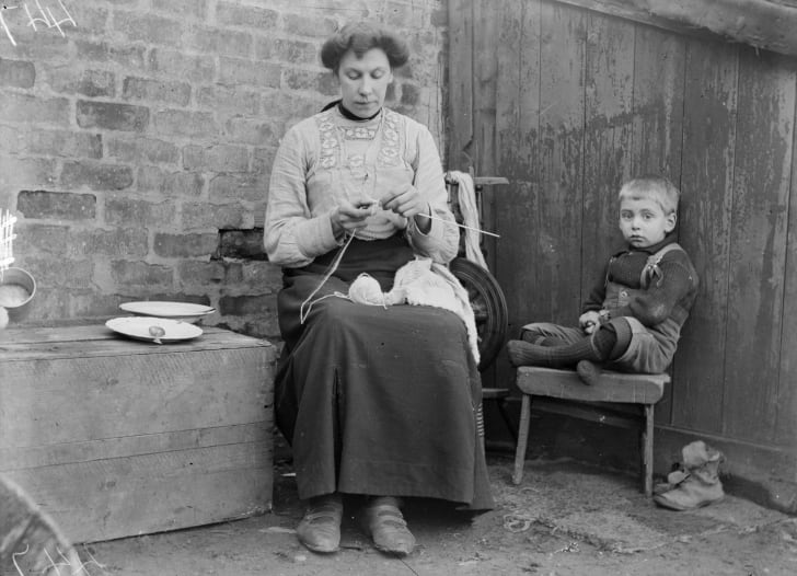 A child sits quietly as his mother knits Shetland wool into jumpers