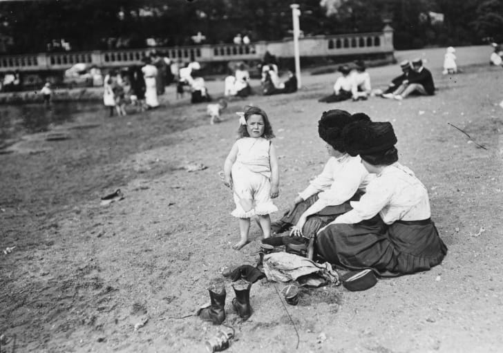 A child plays in the sand with her spade, whilst her mother and aunt look on, at a riverside spot in Fulham, London