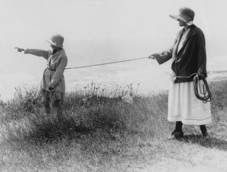 A mother holds a rope attached to her daughter's waist