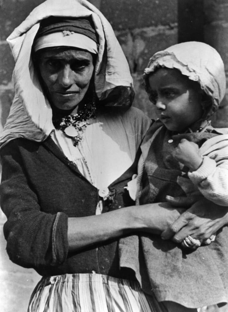 A Palestinian mother in typical dress holding her child