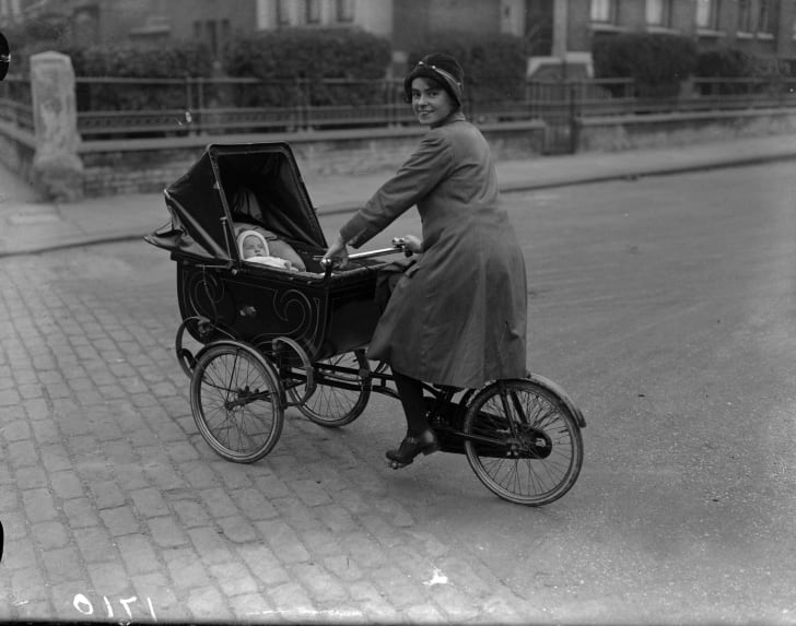 A mother gets all the exercise she needs pushing her pram and cycling at the same time