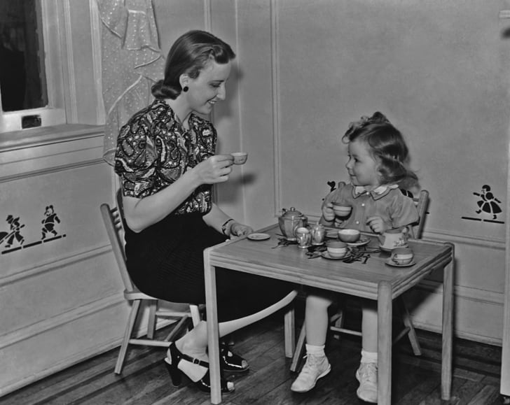 A mother enjoying a tea party with her young daughter circa 1930's