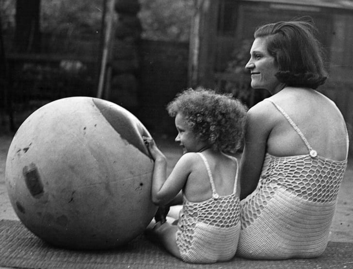 Mother and daughter sunbathing in similar knitted costumes